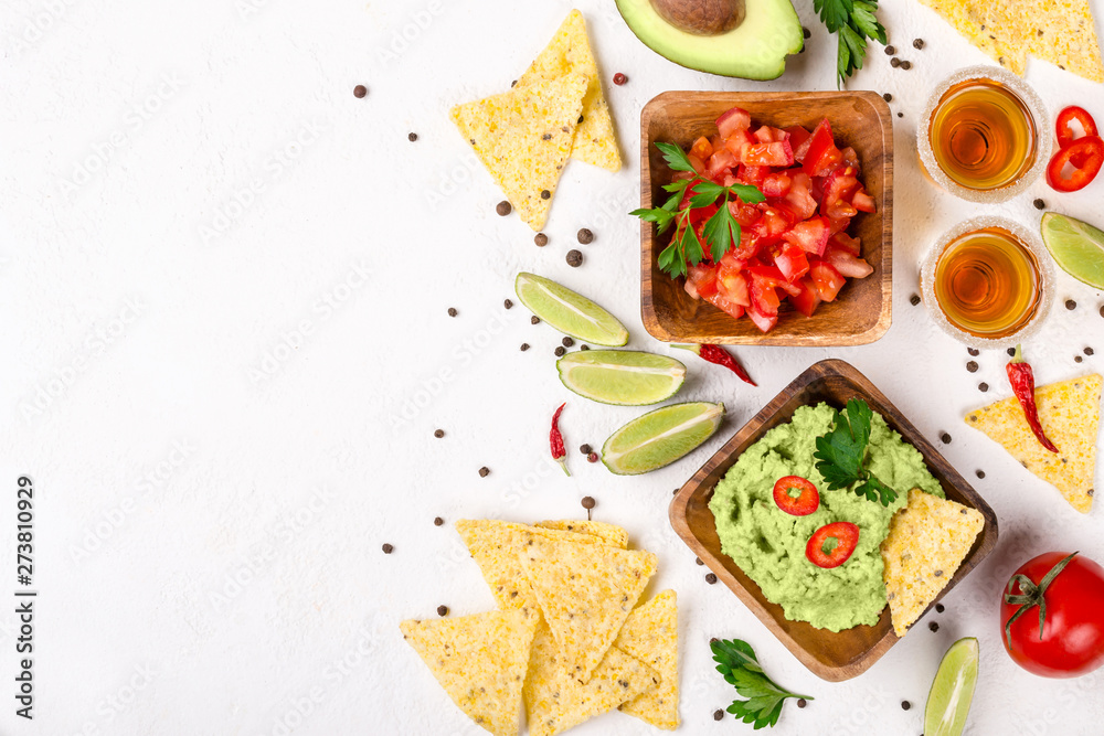 Mexican food selection: sauce guacamole, salsa, chips and tequila shots with lime on white background