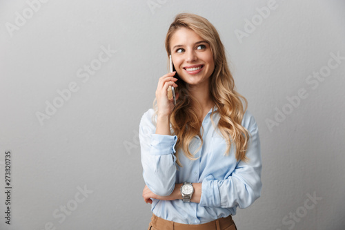 Fotografía  Photo of caucasian blond businesswoman with long curly hair smiling and calling