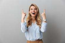 Photo Of Happy Blond Businesswoman With Long Curly Hair Smiling And Pointing Fingers Upward At Copyspace