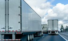 Convoy Of Big Rig Semi Trucks With Semi Trailers Running On The Wide Highway On Several Lines