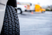 Tire Tread Of Semi Truck Wheel On The Background Of Another Semi Truck Standing On The Parking Lot