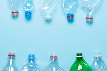 Plastic Bottles On Blue Background Top View. Recycle Plastic Waste Pollution Concept Template.
