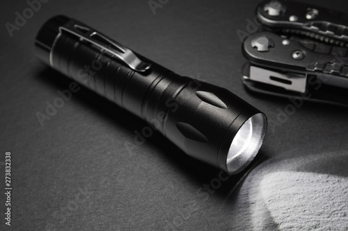 Obraz black flashlight on the stone surface. Tools for work, search and tourism .. - fototapety do salonu
