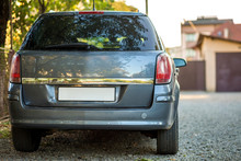 New Shiny Gray Car Parked On Gravel Suburbs Road On Blurred Sunny Summer Background.