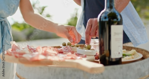 Stampa su Tela Romantic couple, man and woman toasting with red wine and eating finger food appetizer at warm sunset