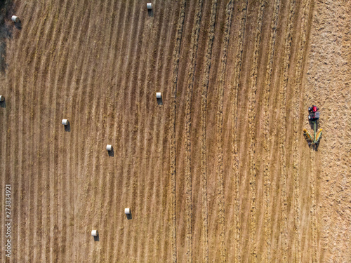 Photo Nature and landscape, aerial view of fields with tractor with round baler and tractor with a rake, machines for collecting and pressing hay