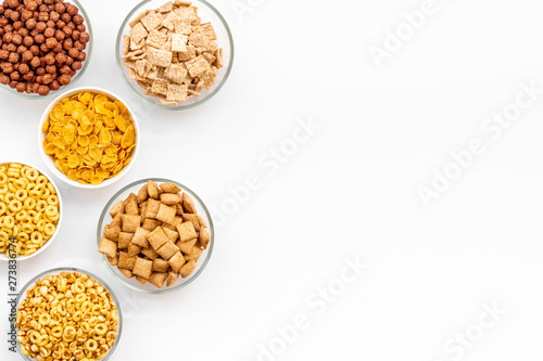 Vászonkép cereals, oatflakes and cornflakes for healthy breakfast on white background top