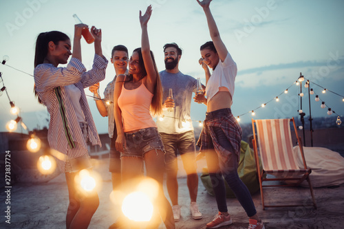 Fototapeta Happy friends with drinks toasting at rooftop party at night obraz