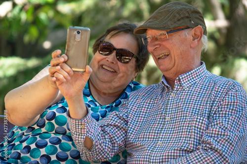 Pareja de gente mayor (un abuelo y una abuela) intentando hacerse un selfie con su teléfono móbil / smartphone en un parque Canvas Print