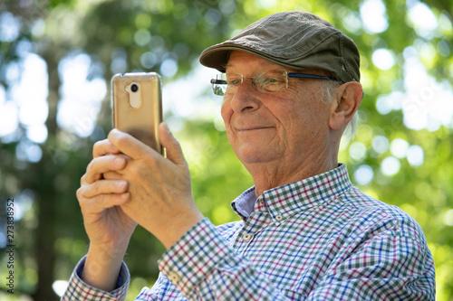 Distintas reacciones de un hombre mayor (abuelo) mirando las llamadas y los mensajes en su teléfono móbil (smartphone) personal Wallpaper Mural