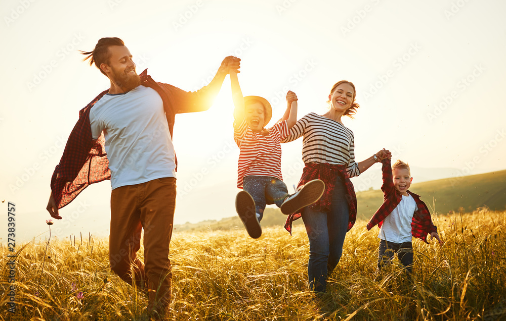 Fototapeta Happy family: mother, father, children son and daughter on sunset.