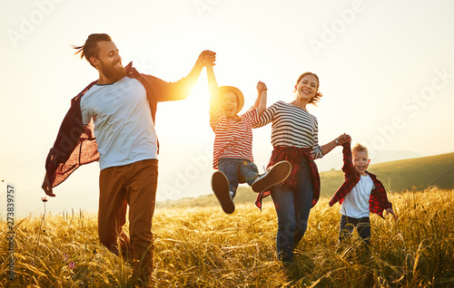 Obraz Happy family: mother, father, children son and daughter on sunset. - fototapety do salonu