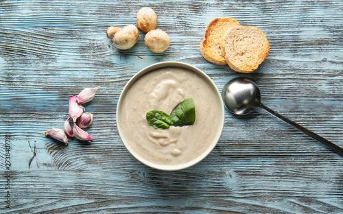 Fototapeta Bowl with delicious mushroom cream soup on wooden table obraz