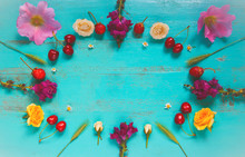 Summer Composition With Flowers, Grass, Cherries, Strawberries Lying As A Frame On An Old Painted Wooden Table. Top View. Image Is With Copy Space