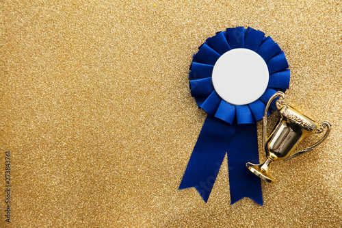 Fotografie, Tablou  Gold winners achievement trophy on a gold glitter background