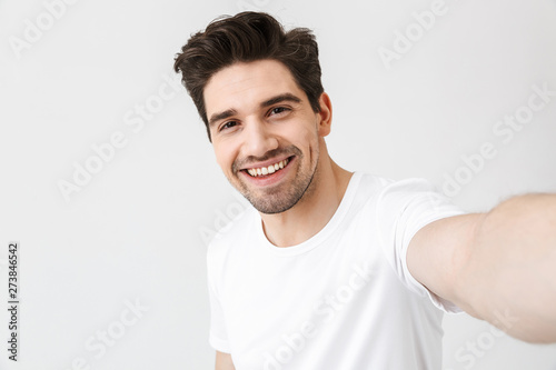 Fotografía Excited happy young man posing isolated over white wall background make a selfie by camera