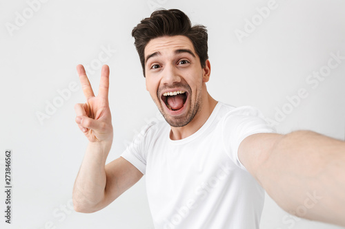 Carta da parati  Excited happy young man posing isolated over white wall background make a selfie by camera