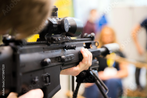 Fotomural  Young soldier aiming machine gun at target during military training in cadet corps