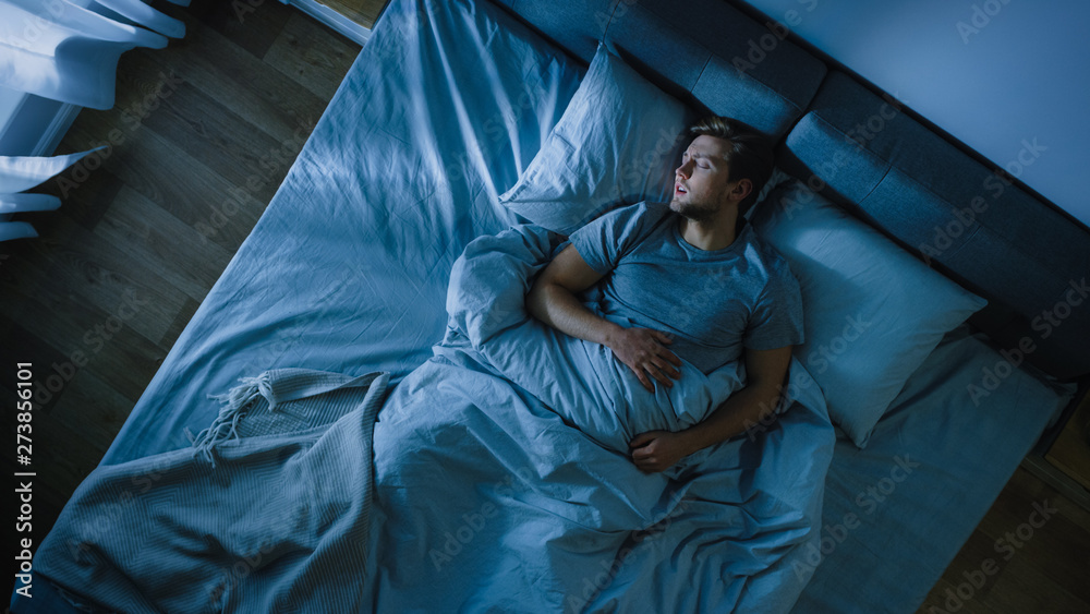 Fototapeta Top View of Handsome Young Man Sleeping Cozily on a Bed in His Bedroom at Night. Blue Nightly Colors with Cold Weak Lamppost Light Shining Through the Window.