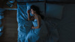 canvas print picture - Top View of Beautiful Young Woman Sleeping Cozily on a Bed in His Bedroom at Night. Blue Nightly Colors with Cold Weak Lamppost Light Shining Through the Window.