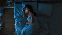 Top View Of Beautiful Young Woman Sleeping Cozily On A Bed In His Bedroom At Night. Blue Nightly Colors With Cold Weak Lamppost Light Shining Through The Window.