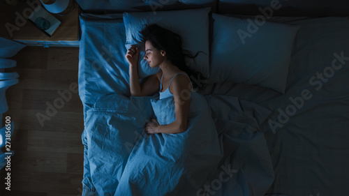 Foto Top View of Beautiful Young Woman Sleeping Cozily on a Bed in His Bedroom at Night