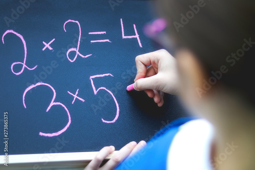 Photo Top view of schoolgirl in glasses doing sums writing on blackboard by chalk