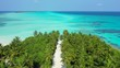 flying over sandy path in palm forest of small desert island in Caribbean sea aerial drone establishing shot