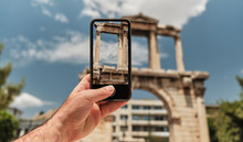 Travel Concept - Tourist Taking Photo With Smart Phone At The Ruins Of Archway Hadrians Arch In A Sunny Day In The Capital Of Greece - Athens.