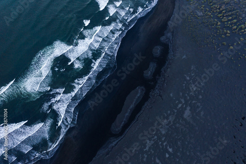 Obraz na płótnie Aerial shot of black stone beach with waves.