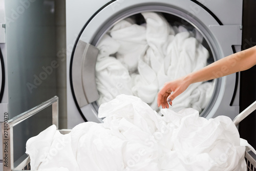 Canvas Print cropped view of housemaid near white bed sheets in laundry