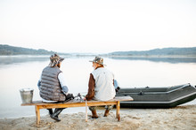 Grandfather With Son Sitting Together On The Bench While Fishing On The Lake Early In The Morning, Back View