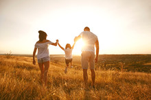 Happy Family On Nature In Summer At Sunset.