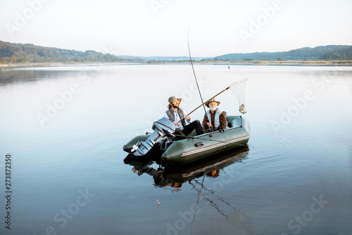 Fotografia, Obraz Grandfather with adult son fishing on the inflatable boat on the lake with calm water early in the morning