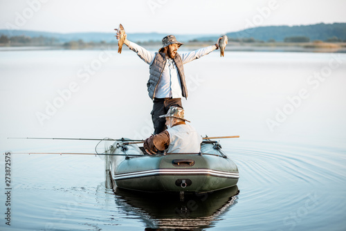 Canvastavla Happy man holding freshly caught fish while standing on the boat with grandfathe