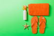 Leinwandbild Motiv Top view of Beach flat lay accessories. sunscreen bottle with seashells, starfish, towel and flip-flop on Colored background with copy space