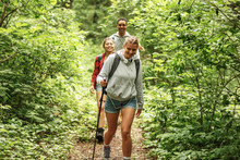 Group Of Friends Hiking In Nature.They Walking Trough Forest And Meadows.Blond Hair Female Are In Focus.