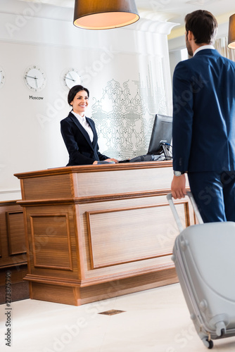 selective focus of attractive receptionist looking at businessman walking with luggage