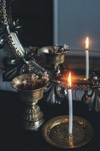 Mirror Magick Witchcraft - Scrying With A White Lit Burning Candle To Read The Flame. A Reflection In A Dark, Moody Vintage Mirror With Gold Brass Colored Antique Items - Candle Holder, Incense Burner