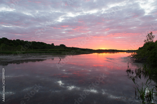 Spectacular cloudy sunrise on the Léon-Provancher marsh during springtime, Neuville, Quebec, Canada #273899929