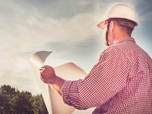 Handsome Engineer In A White Hard Hat, Holding A Paper Project In The Park Against The Backdrop Of Green Trees And The Setting Sun, Looking Into The Distance. Close-up. Concept Of Labor And Employment