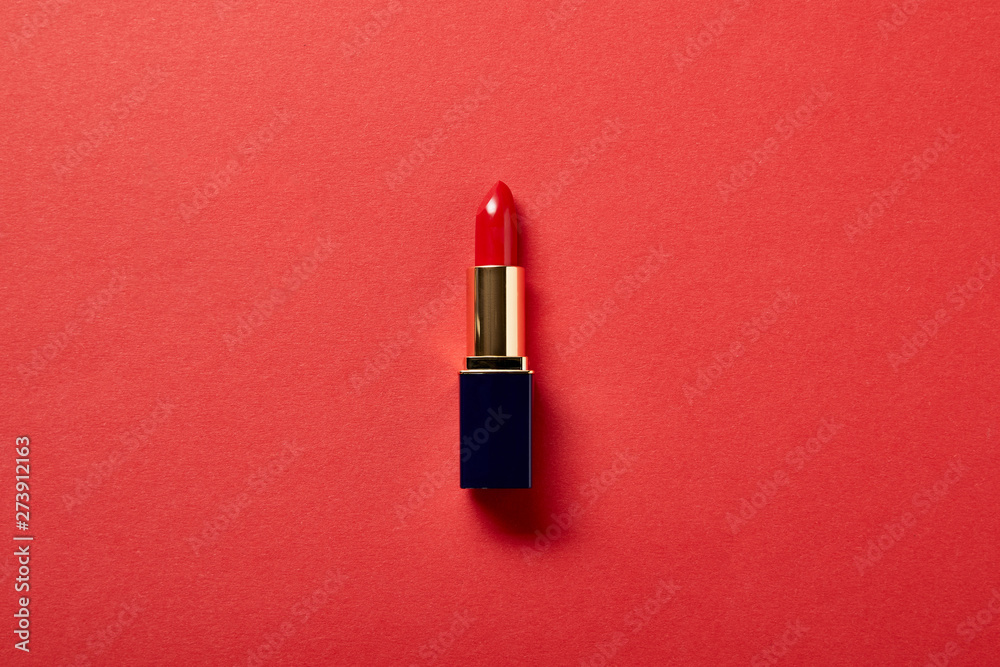 Fototapety, obrazy: top view of single tube of red lipstick on red