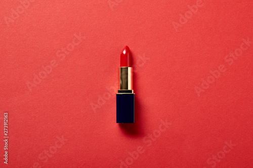 Canvastavla top view of single tube of red lipstick on red