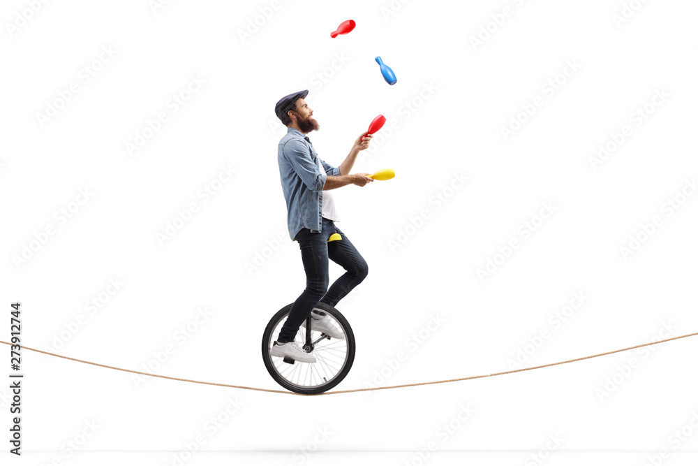 Fototapety, obrazy: Male juggler with clubs riding a unicycle on a rope
