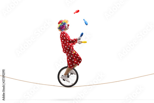 Fotografia Clown juggling with clubs and riding a unicycle on a rope