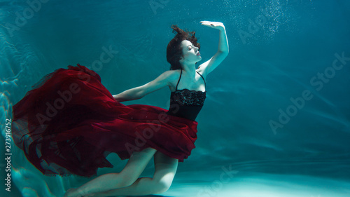 beautiful girl in a red dress swims under water Poster Mural XXL