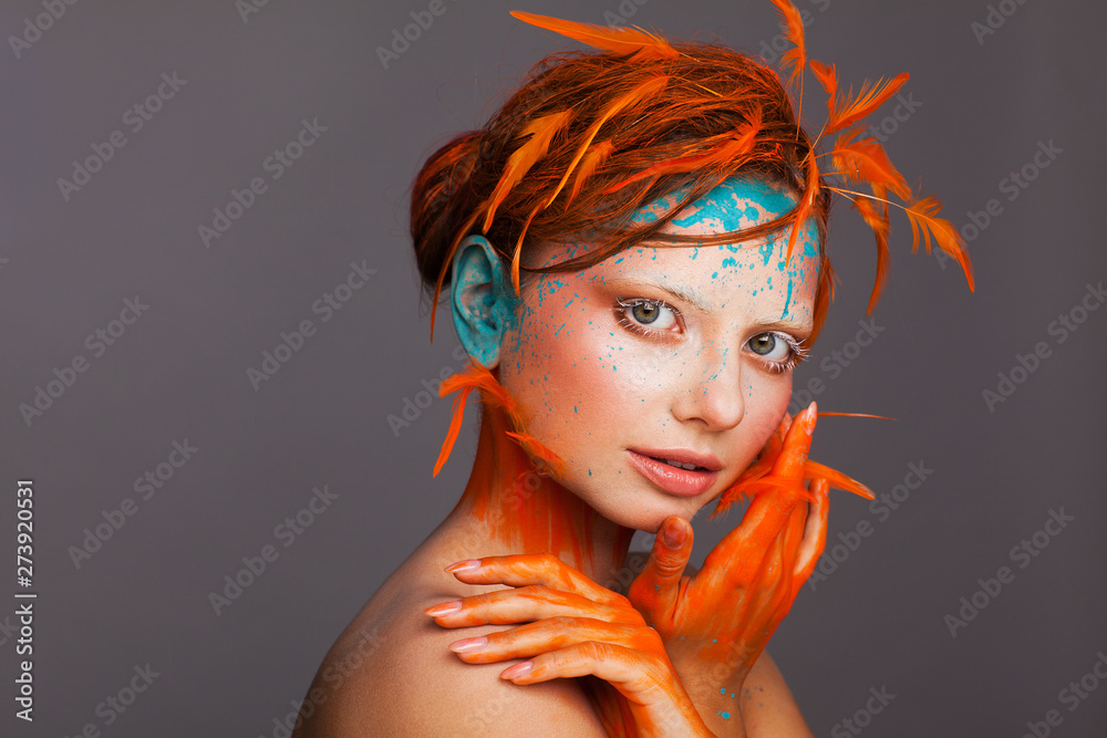 Fototapety, obrazy: Portrait of a beautiful model with creative make-up and hairstyle using orange feathers