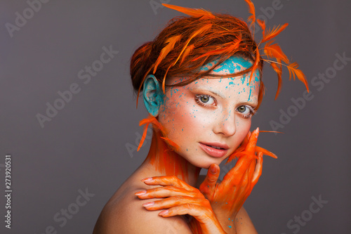 Tela Portrait of a beautiful model with creative make-up and hairstyle using orange f