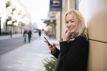 Portrait Of Smiling Young Woman With Cell Phone In The City