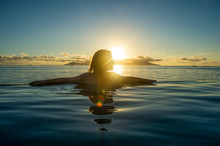French Polynesia, Tahiti, Papeete, Woman Enjoying The Sunset In An Infinity Pool